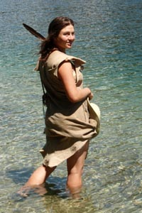 Katie in buckskins wading in lake.