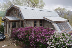 Barn style, slipform stone masonry home in Silver Star, MT with lilac hedge.